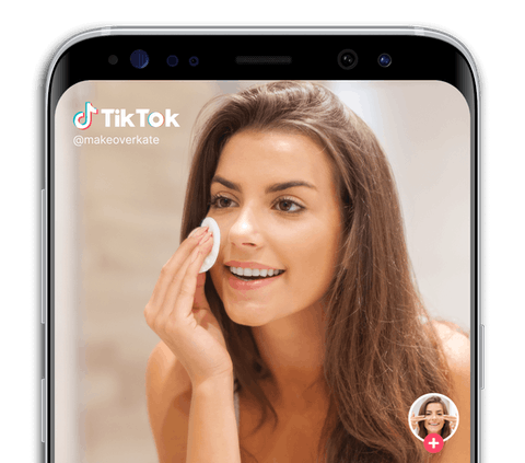 A phone showing a TikTok video of a makeover using makeup.