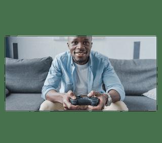 A PlayStation gamer on a sofa.