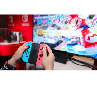 Playing Mario Kart on Nintendo Switch connected to a TV.